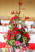 Vase of red flowers on a red tablecloth — Stock Photo