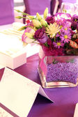 Arrangement of a bouquet of purple flowers on purple tablecloth — Stock Photo