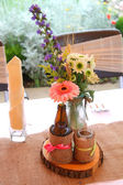 Vintage table decoration with flowers and glass bottles — Stock Photo