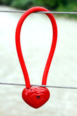 Metal padlock in the form of heart on fence, symbol of love — Stock Photo