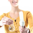Girl holding a energy-saving lamp and a light bulb — Stockfoto