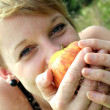 Girl with apple on summer meadow — Stock Photo
