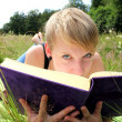 Girl is reading a book on a summer meadow — Stock Photo