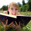 Stock Photo: Girl is reading a book on a summer meadow