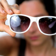 Stock Photo: Young womholding sunglasses