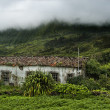 Stock Photo: Old building and cloudy mountains of flores acores islands