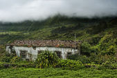 Old building and cloudy mountains of flores acores islands — Stock Photo