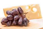 Cheese and dark grapes — Stock Photo