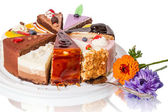 Different pieces of cake and flower — Stock Photo