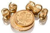 Gouden tandheelkundige kronen en oude munten — Stockfoto