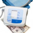Digital blood pressure monitor and dollar cash - Stok fotoğraf