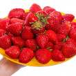 Hand with ripe strawberries on a yellow plate — Stock Photo #48681499