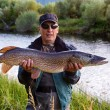 Stock Photo: Fishermwith pike fish