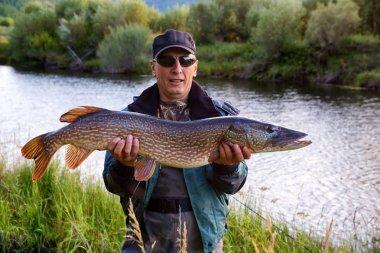 Fisherman with pike fish