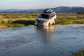 Tourists in cars crossing small river — Stock Photo