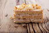 Piece of creamy hazelnut cake on old wooden table — Stock Photo