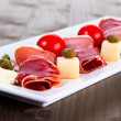 Slices of Delicious Prosciutto with capers, olives and cheese — Stock Photo