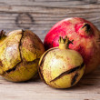 Ripe pomegranate on the old wood background — Stock Photo