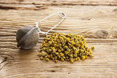Dry camomile with tea strainer on old wooden table — Stock Photo