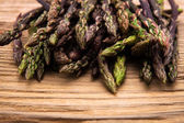 Wild asparagus close up on old wooden background — Stock Photo