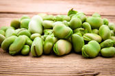 Fresh broad bean on old wooden background — Stok fotoğraf