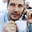 Young businessman drinking coffee and speaking on the phone — Stock Photo