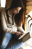 Girl looking at tablet in cafe showing emotion — Stockfoto