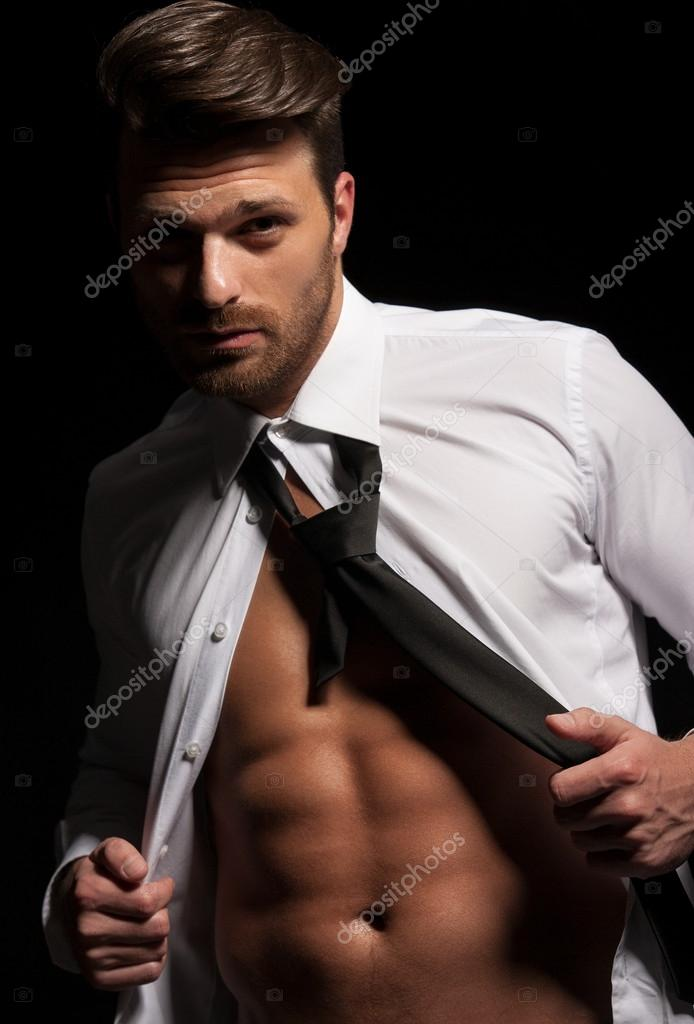 Man in suit showing abs a result of hard workout — Stock Photo © Markomarcello #45340441