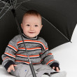 Baby boy sitting under umbrella — Stock Photo