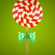 Lollipop with bow on green background — Stock Photo