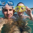 Lovely couple enjoying snorkeling during their vacation - Stock Photo
