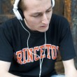 Man listening to the music in a park with white headphones — Stockfoto