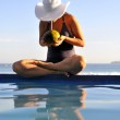 Woman relaxing on a swimming pool with a sea view — Stock Photo #14763687