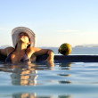 Woman relaxing on a swimming pool with a sea view — ストック写真