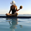 Woman relaxing on a swimming pool with a sea view — Stock Photo #14763745