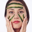 Young woman with her face covered with cucumber slices — Stock Photo #10772111