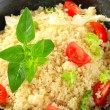 Couscous with salad greens and tomato - Stock Photo