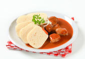 Pork meat in tomato sauce with dumplings — Stock Photo