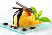 Ice cream with chocolate sauce and mint sticks — Stock Photo