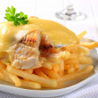 Cheese topped fish fillets with French fries — Stock Photo