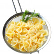 Bow tie pasta in a sieve - Stock Photo