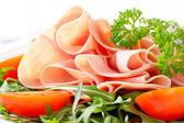 Sliced ham with arugula leaves and tomatoes — Stock Photo