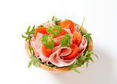 Sliced ham with arugula and tomatoes — Stock Photo