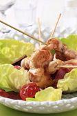 Chicken skewers on lettuce leaves — Stock Photo