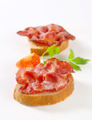 Crispy slices of pork meat on bread — Stock Photo