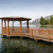 Wooden pier and gazebo on a lake — Stock Photo