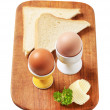Boiled eggs in eggcups and white bread — Stock Photo