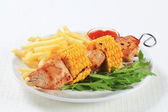 Turkey and sweetcorn skewer with French fries — Stock Photo