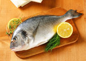 Fresh sea bream on cutting board — Stock Photo