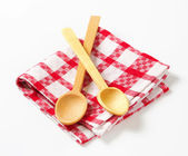 Checked tea towel and wooden spoons — Stock Photo